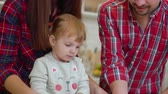 segít : young parents with toddler daughter have fun with dough in kitchen Stock mozgókép