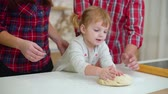 tata : little girl kneading dough and parents helping her