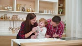 3 : happy young parents with toddler daughter having fun with flour in kitchen 動画素材