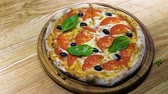 пищевой продукт : hands in gloves decorate fresh baked pizza with basil leaves in slow motion Стоковые видеозаписи