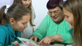 アーカイブ : closeup of grandmother showing old photo album to her granddaughters