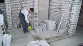 construction worker moisturing concrete foundation with water sprayer Стоковые видеозаписи