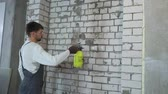 construction worker moisturing brick wall with water sprayer