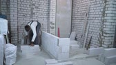 builder sawing aerated concrete block with hand saw