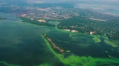 rebut : aerial of wide river infected with green algae near big industry zone