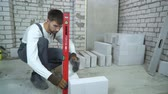 check quality : construction worker laying aerated concrete block according to bubble level