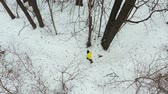 maraton : aerial pan shot of male runner in yellow coat training in forest on winter day