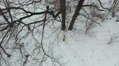springseil : aerial of young man in yellow coat exercising with jumping rope in winter forest Stock Footage