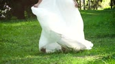 gown : low shot of bride turning around in sunny garden in slow motion Stock Footage