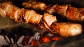 fornalha : closeup of turning meat skewers while roasting on charcoal grill