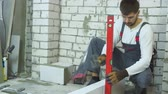nível : builder fixing brick laying with rubber hammer according to bubble level
