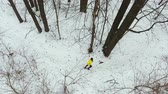 aerial pan shot of male sportsman in yellow coat jogging in winter forest