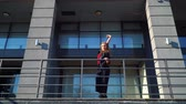 korkuluk : blonde woman street dancer performing near metal railings of modern building Stok Video
