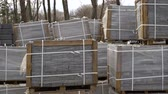 adoquin : paving stones packed in stacks and wrapped in film are stored on ground outdoors Archivo de Video