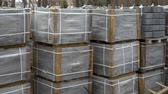 grundriss : pan shot of stacks of paving stones wrapped in construction film stored outdoors