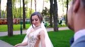 wedding veil : happy young bride walking around groom standing still in sunny park