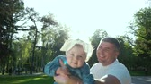 楽しんで : father swings his little daughter on his arms in summer park with lens flare
