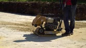 компактный : partial view of worker using vibratory plate compactor at construction site