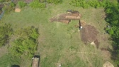 heavy : aerial of digging foundation pit for new house by mini loader and excavator Stock Footage