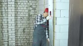 quality time : man in work wear and red cap uses construction ruler to check quality of wall