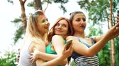 holi : low angle of happy girls laugh and make selfies after Holi festival in park