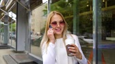 fede nuziale : smiling blonde married woman talking on mobile phone on city street