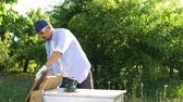 backyard : woodworker in protective glasses polishes wooden plank with electric sander