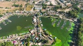 rebut : aerial of river bay polluted with green algae with huts and boat docks on banks