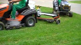 mowing : crop shot of workers riding on industrial lawn mowers and cutting grass in park Stock Footage