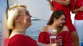 kırmızı şarap : Women in red outfits enjoing trip on sailing boat
