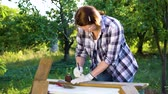 móveis : female carpenter measures wooden plank with measuring tape in sunny garden