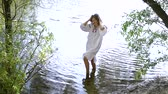 açık : Girl in ethnic dress standing in river and touching her hair Stok Video