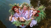 ukrán : Four women in floral circlets standing in water