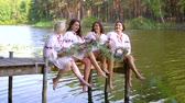pontão : Pretty women in ethnic dresses with floral circlets sitting on wooden bridge