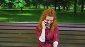 jovial : Happy red haired girl talking to friend on mobile phone in park