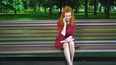 jovial : Happy red haired girl chatting joyfully on mobile phone in park