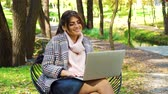 jovial : Happy freelancer sitting in garden and having video call on laptop