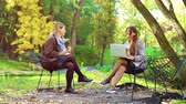 jovial : Young freelancers working remotely in autumn park Stock Footage