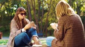 차림새 : Emotionless girls addicted with smartphones in sunny park