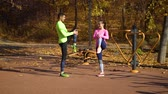 encajar : Athletic couple warming up and stretching legs on sports ground on autumn day Archivo de Video