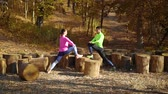 entrar : Couple of athletes stretching legs on wood logs in autumn forest Stock Footage