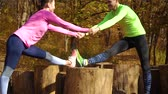 entrar : Athletic couple holding hands and training together in autumn forest