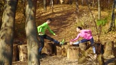 Happy couple training together on wood stumps in autumn forest