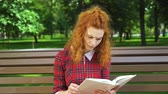 Unhappy red haired girl reading thriller in park