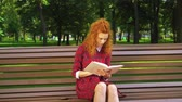 encaracolado : Pretty girl reading sad book in green park