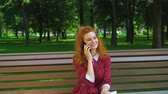 jovial : Jovial red haired girl talking on smartphone in park and laughing