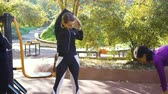 Fit girls doing exercises for back and arms on sports ground Stock Footage