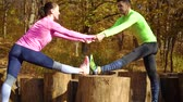 entrar : Happy couple holding hands and exercising in autumn forest Vídeos