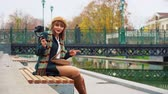 Elegant girl vlogger recording video in park using smartphone with steadicam