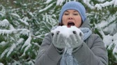 smiling woman blowing snow in pine forest on winter day in slow motion Stock Footage
